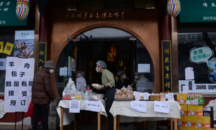 A customer wearing a face mask buys vegetables from a stall set up by a hotpot restaurant outside its outlet in central Beijing, following an outbreak of the novel coronavirus in China, on Feb. 13, 2020. (Tingshu Wang/Reuters)