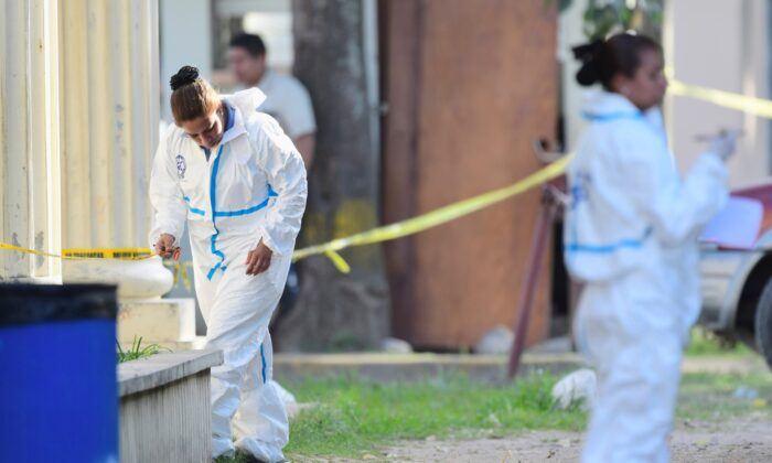Members of a forensic team work at a crime scene where about 20 gunmen killed three policemen and wounded two others, in El Progreso, Honduras, on Feb. 13, 2020. (Roberto Amaya/Reuters)