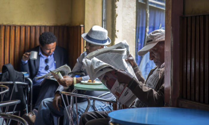 Ethiopian men read newspapers and drink coffee at a cafe during a declared state of emergency and internet shurdown in Addis Ababa on Oct. 10, 2016. (Mulugeta Ayene/AP)