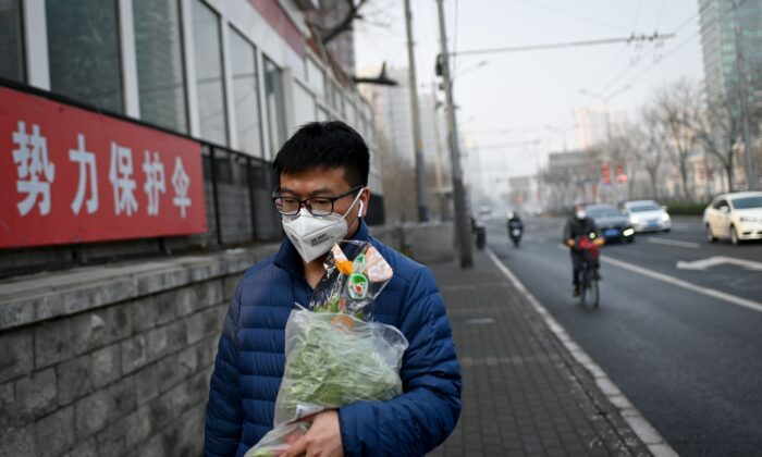 A man wearing a face mask and holding a bag of vegetables walks along a street in Beijing on Feb. 12, 2020. (STR/AFP via Getty Images)