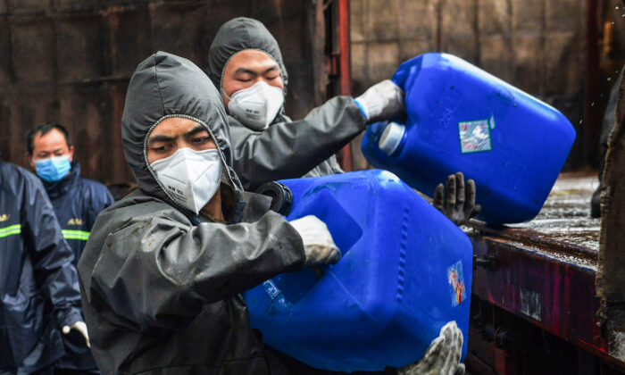 Chinese paramilitary police officers wearing protective gears transfer pails of disinfectant in Yunmeng County outside Xiaogan City in China's central Hubei province on Feb. 12, 2020. (STR/AFP via Getty Images)