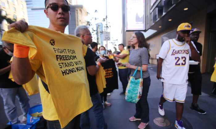 A pro-Hong Kong activist (L) hands out t-shirts before the Los Angeles Lakers season opening game against the LA Clippers outside Staples Center in Los Angeles on Oct. 22, 2019 (Mario Tama/Getty Images)