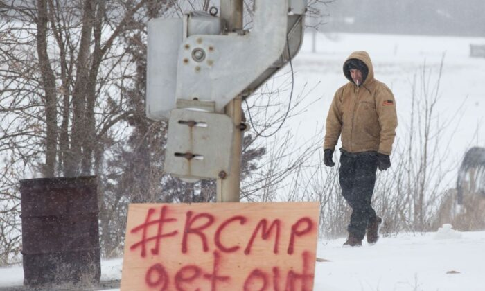 A man walks past a sign put up by protesters blocking the CN tracks in Tyendinaga, Ont., on Feb.7, 2020, in support of the Wet'suwet'en members' blockade of a natural gas pipeline in northern B.C. (The Canadian Press/Lars Hagberg)