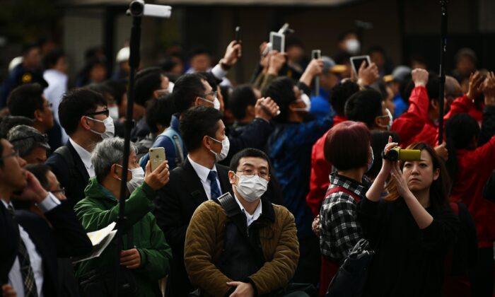 People wearing facemasks look on during a rehearsal of the Tokyo 2020 Olympics torch relay in Tokyo on Feb. 15, 2020. (Charly Triballeau/AFP via Getty Images)