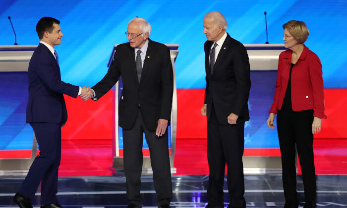 Democratic presidential candidates former South Bend, Indiana Mayor Pete Buttigieg and Sen. Bernie Sanders (I-VT) shake hands as former Vice President Joe Biden and Sen. Elizabeth Warren (D-MA) look on prior to the start of the Democratic presidential primary debate in the Sullivan Arena at St. Anselm College on Feb. 07, 2020 in Manchester, New Hampshire. (Joe Raedle/Getty Images)