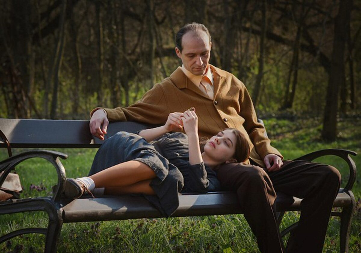 man and girl on park bench