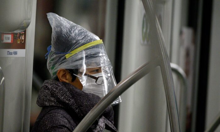 A subway passenger wears a facemask among other protective items in Shanghai on Feb. 12, 2020. (NOEL CELIS/AFP via Getty Images)