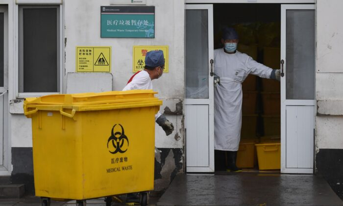 A worker carts a bin loaded with medical waste to a storage facility at the You'an Hospital in Beijing, China, on Feb. 14, 2020. (Greg Baker/AFP via Getty Images)