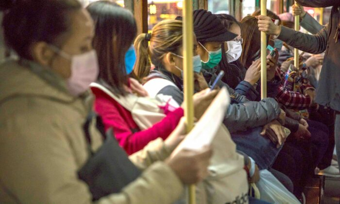 People wearing protective face masks commute on a tram in Hong Kong on Feb. 9, 2020. (Dale De La Rey/AFP via Getty Images)