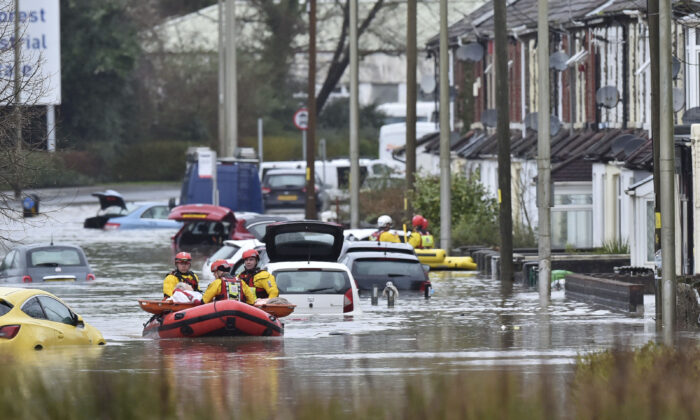A member of the public is rescued after flooding in Nantgarw, Wales, on Feb. 16, 2020. (Ben Birchall/PA via AP)