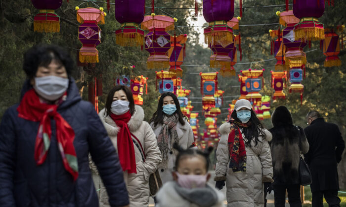 Residents wear protective masks as they walk under Chinese New Year decorations in a park in Beijing, China on Jan. 25, 2020. (Kevin Frayer/Getty Images)