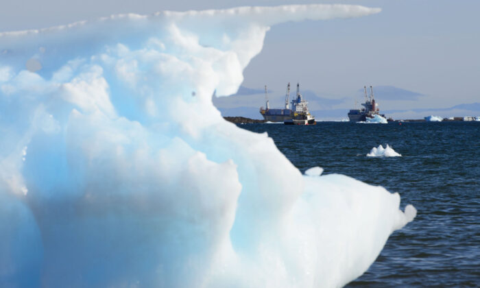 Ships are framed by pieces of melting sea ice in Frobisher Bay in Iqaluit, Nunavut, on July 31, 2019. (Sean Kilpatrick/The Canadian Press)