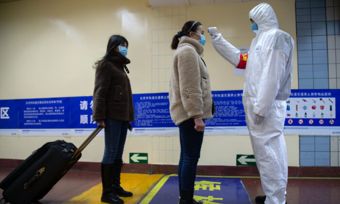 A health worker checks the temperature of women entering the subway, screening for possible coronavirus cases, in Beijing, China, on Jan. 26, 2020. (Betsy Joles/Getty Images)