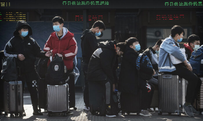 Chinese students wear masks as they wait to take a train after Chinese New Year break in Beijing, China, on Jan. 31, 2020. (Kevin Frayer/Getty Images)