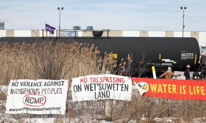 Banners hang on a fence as protesters stage a blockade of the rail line at Macmillan Yard in Toronto, on Feb. 15, 2020. (Chris Young/Canadian press)