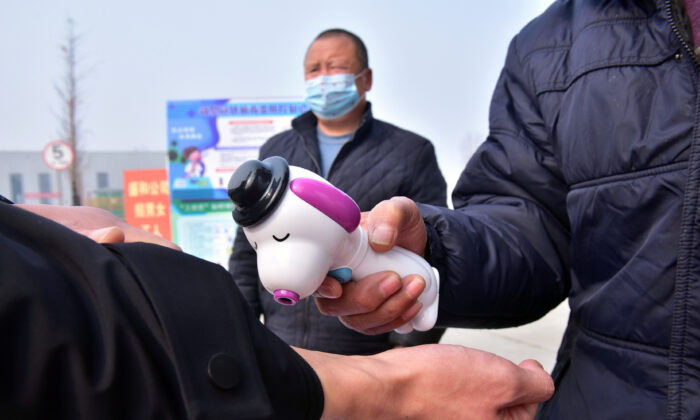 A guard measures the body temperature of a worker with a thermometer at the entrance to a factory, as the country is hit by an outbreak of the novel coronavirus, in Shijiazhuang, Hebei Province, China on Feb. 13, 2020. (China Daily via Reuters)