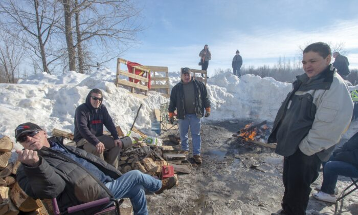 Members of the Mohawk community man a blockade of the commuter rail line in Kahnawake, Quebec, on Feb. 12, 2020. (The Canadian Press/Ryan Remiorz)