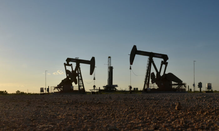 Pump jacks operate in front of a drilling rig in an oil field in Midland, Texas, on Aug. 22, 2018. (Nick Oxford/Reuters/File)