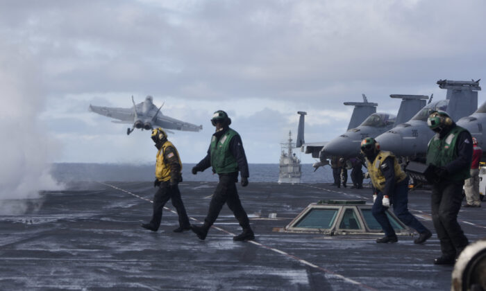 Sailors stand on the flight deck after launching an F/A-18F Super Hornet from the the Nimitz-class aircraft carrier USS Harry S. Truman (CVN 75) in the North Atlantic on Sept. 18, 2018. (2nd Class Anthony Flynn/DoD)