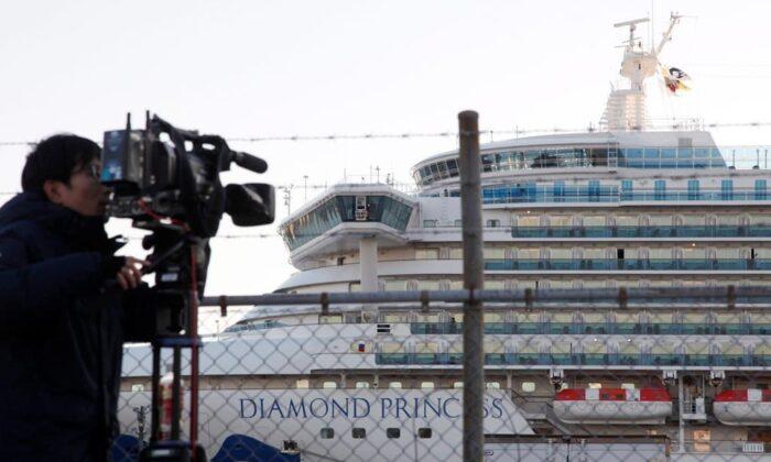 A TV cameraman films the quarantined ship Diamond Princess, anchored at Yokohama port in Yokohama, near Tokyo, on Feb. 18, 2020. (AP Photo/Koji Sasahara)