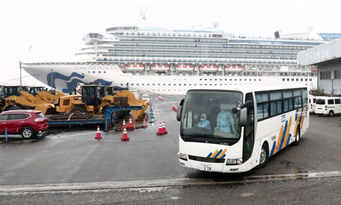 A bus with a driver (L) wearing protective gear departs from the dockside next to the Diamond Princess cruise ship, at the Daikoku Pier Cruise Terminal in Yokohama port in Japan on Feb. 16, 2020. (Behrouz Mehri/AFP via Getty Images)
