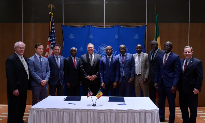 U.S. Secretary of State Mike Pompeo (C,L) and Senegal's Economy, Planning and International Cooperation minister Amadou Hott (C,R) pose with (from L) the President of Weldy-Lamont Patrick Hennelly, ABD Group CEO John Nevergole, General Electric CEO Farid Fezoua, U.S. Ambassador to Senegal Tulinabo Mushingi, Senegalese Ambassador to the United States Mansour Kane, the Director General for Ageroute Ibrahima Ndiaye, an unidentified person, the Director General of Senelec Pape Biteye, and the President of Bechtel Stuart Jones after they signed a memorandum of understanding in Dakar on Feb. 16, 2020. (Andrew Caballero-Reynolds / Pool/ AFP via Getty Images)