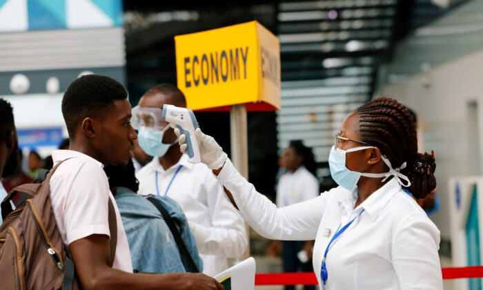 A health worker checks the temperature of a man as part of the coronavirus screening procedure at the Kotoka International Airport in Accra, Ghana on Jan. 30, 2020. (Francis Kokoroko/Reuters)