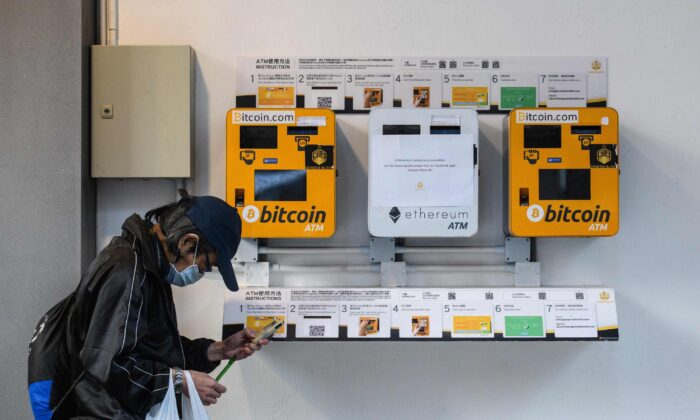 A man uses his phone as he walks past ATM machines for digital currency Bitcoin in Hong Kong on Dec. 18, 2017. (Anthony Wallace/AFP via Getty Images)