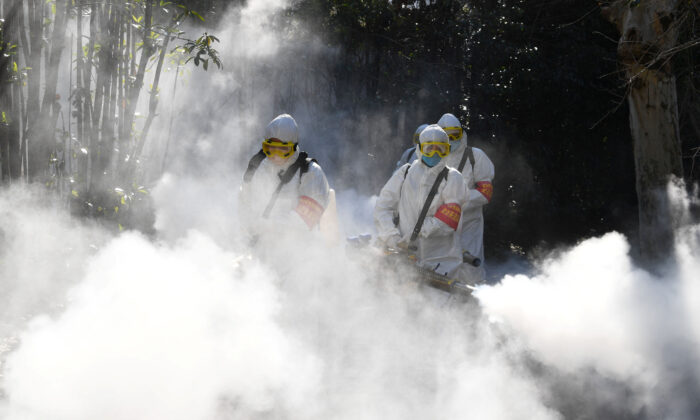 Sanitation workers disinfect a residential compound, as China is hit by an outbreak of the novel coronavirus in Bozhou in Anhui Province, China on Feb. 18, 2020. (China Daily via Reuters)