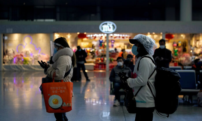 Travelers with face masks and shields are seen at the Shanghai Hongqiao Railway Station on the last day of the Spring Festival travel rush, as the country is hit by an outbreak of the novel coronavirus, in Shanghai, China on Feb. 18, 2020. (Aly Song/Reuters)
