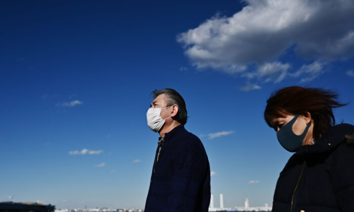 People wearing face masks walk by the coast in Yokohama, Japan on Feb. 18, 2020. (Charly Triballeau/AFP via Getty Images)