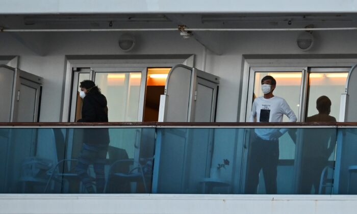 People still in quarantine due to fears of the new COVID-19 coronavirus stand on balconies of the Diamond Princess cruise ship docked at the Daikoku Pier Cruise Terminal in Yokohama, Japan on Feb. 18, 2020. (Charly Triballeau/AFP via Getty Images)