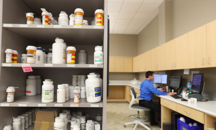A pharmacy technician works on a computer as drug bottles sit on shelves at the central pharmacy of Intermountain Heathcare in Midvale, Utah, on Sept. 10, 2018.   George Frey/Getty Images