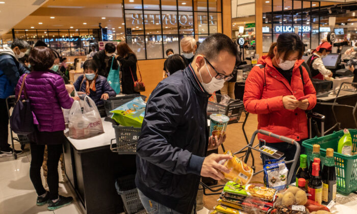 Shoppers wearing face masks bag up their purchases at a grocery store in Hong Kong on Feb. 9, 2020. (Anthony Kwan/Getty Images)