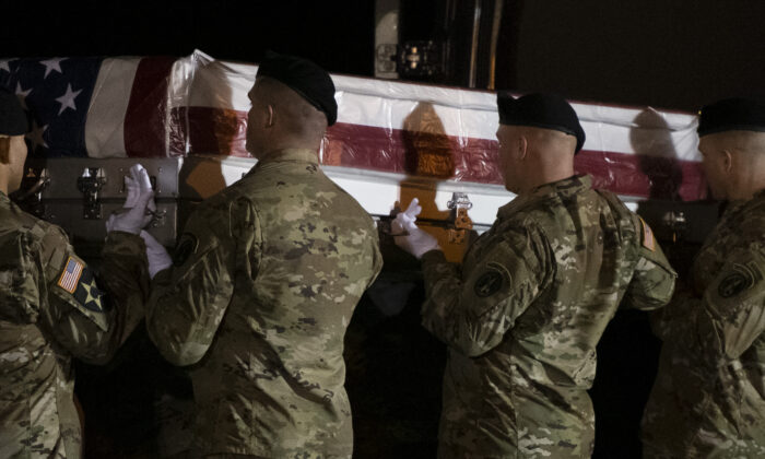 Military personnel lift a transfer case for fallen service member, U.S. Army Sgt. 1st Class Antonio R. Rodriguez, 28, during a dignified transfer at Dover Air Force Base in Dover, Del., on Feb. 10, 2020.  (Mark Makela/Getty Images)