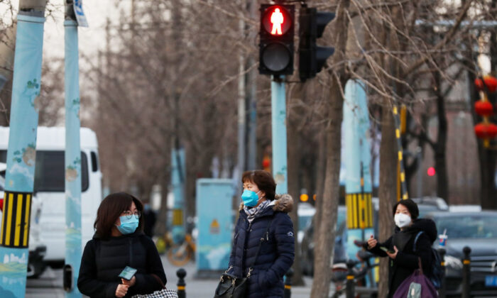 Chinese women wear a mask as they wait to cross a street in Beijing on Feb. 18, 2020. (Lintao Zhang/Getty Images)
