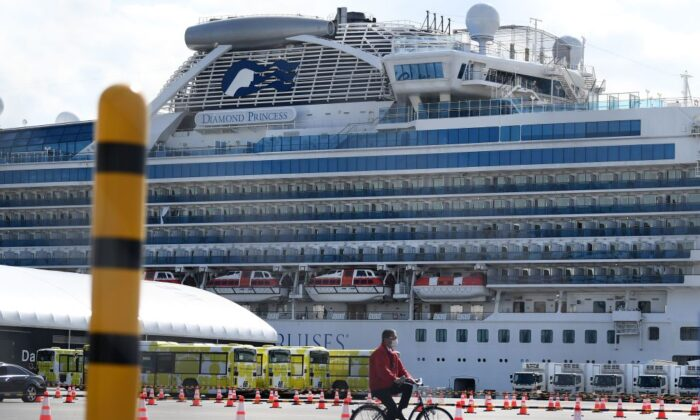 A man cycles past city buses (back L) lined up to transport the first batch of passengers disembarking from the Diamond Princess cruise ship at the Daikoku Pier Cruise Terminal in Yokohama on Feb. 19, 2020. (Charly Triballeau/AFP via Getty Images)