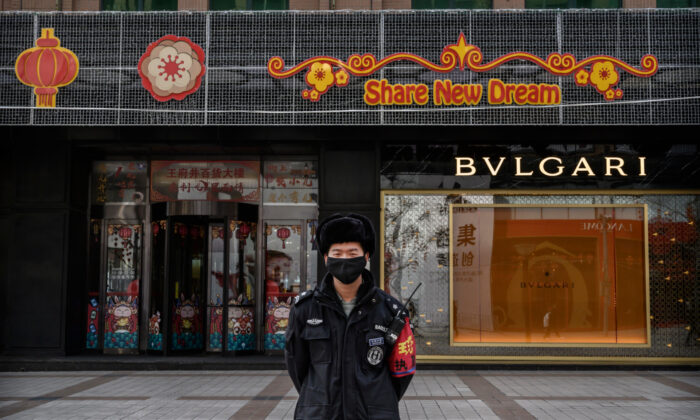 A Chinese security guard wears a protective mask as he stands on a commercial street in Beijing, China, on Feb. 18, 2020. (Kevin Frayer/Getty Images)