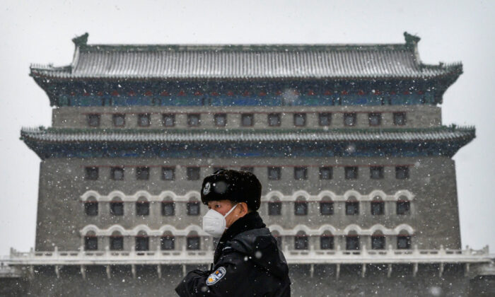 A Chinese police officer wears a protective mask as he stands guard outside the Qianmen Gate during a snowfall in an empty and shuttered commercial street in Beijing, China, on Feb. 5, 2020. (Kevin Frayer/Getty Images)