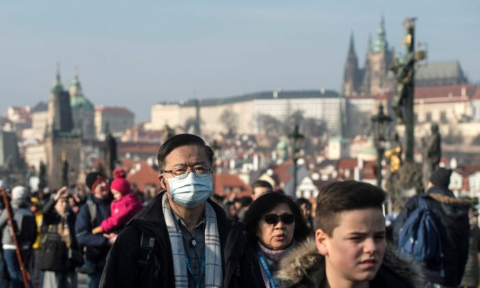 People wear mask as they walk on the Charles bridge in Prague, Czech Republic on Jan. 27, 2020. (Michal Cizek/AFP via Getty Images)
