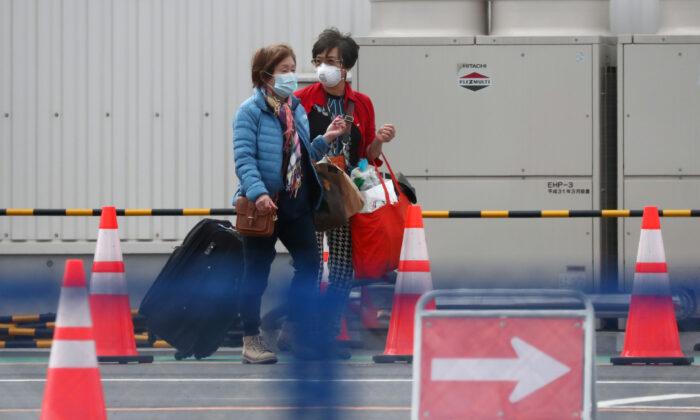 Passengers walk out from the cruise ship Diamond Princess at Daikoku Pier Cruise Terminal in Yokohama, south of Tokyo, Japan on Feb. 19, 2020. (Athit Perawongmetha/Reuters)