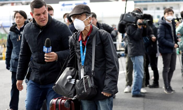 A reporter approaches a passenger after he walked out from the cruise ship Diamond Princess at Daikoku Pier Cruise Terminal in Yokohama, south of Tokyo, Japan, on Feb. 19, 2020. (Athit Perawongmetha/Reuters)