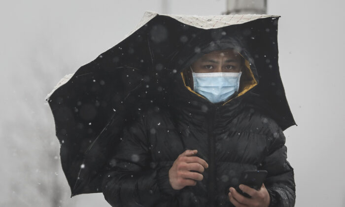 A man wears a protective mask as he holds an umbrella on the Yangzi river bridge as snow falls in Wuhan, Hubei, China, on Feb. 15, 2020. (Getty Images)