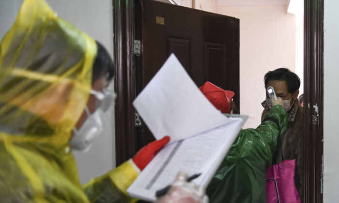 Workers go door to door to check the temperature of residents during a health screening campaign in the Qingheju Community, Qingshan District of Wuhan in central China's Hubei Province. (Cheng Min/Xinhua via AP)