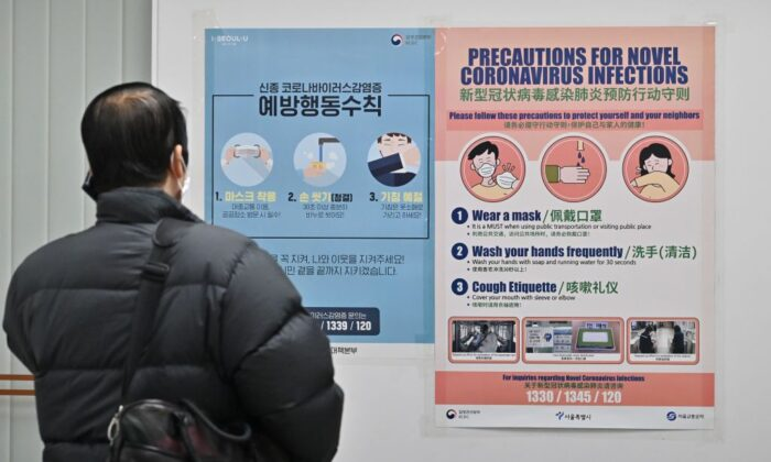 A man wearing a face mask talks on his mobile phone in front of a poster about precautions against the novel coronavirus that originated in central China, at a subway station in Seoul on Feb. 10, 2020. (Jung Yeon-je/AFP via Getty Images)