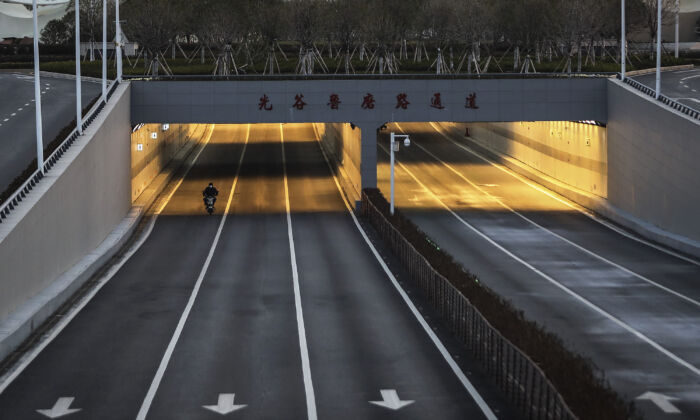 A man is cycling in the empty street at Optical Valley in Wuhan, China on Feb. 16, 2020. (Getty Images)