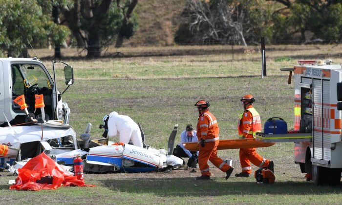 Emergency service personnel attend to the wreckage of a light aircraft on a property at Avenel in Victoria, Australia, on Feb. 19, 2020. (AAP Image/James Ross)