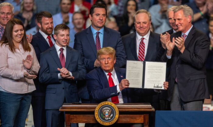 President Donald Trump ceremonially signs legislation at a rally with local farmers in Bakersfield, California, on Feb. 19, 2020. (David McNew/Getty Images)