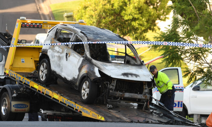 A tow truck operator removes a car from the scene of a car fire which claimed the lives of a man and his three children in Brisbane, Feb. 19, 2020. (AAP Image/Dan Peled)