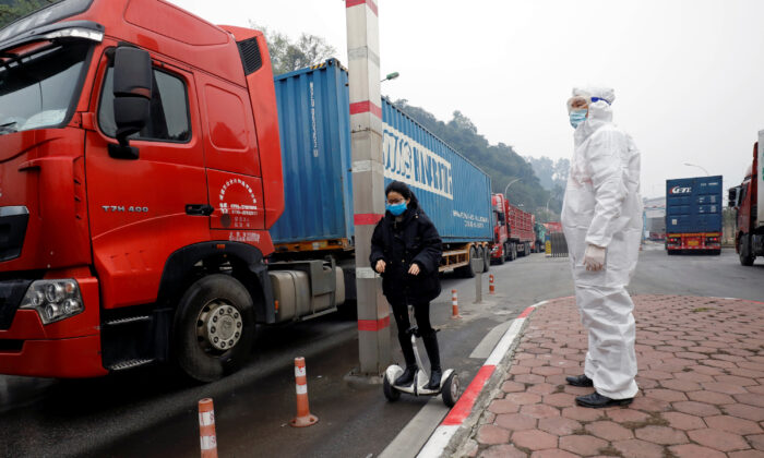 A Vietnamese health worker looks on as a Chinese trader in protective mask rides a hoverboard along container trucks going from China to Vietnam, at Huu Nghi border gate connecting with China, in Lang Son province, Vietnam on Feb. 20, 2020. (Kham/Reuters)